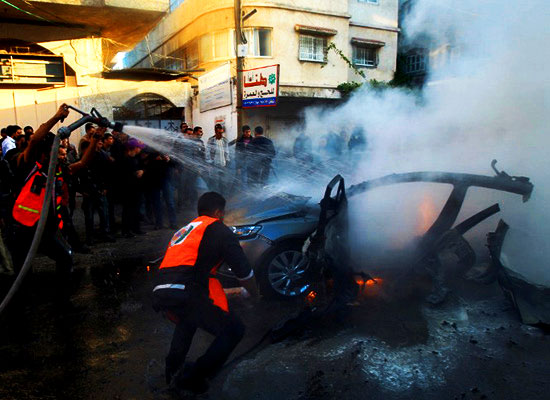 Palestinians extinguish fire from the car of Ahmaed Jaabari